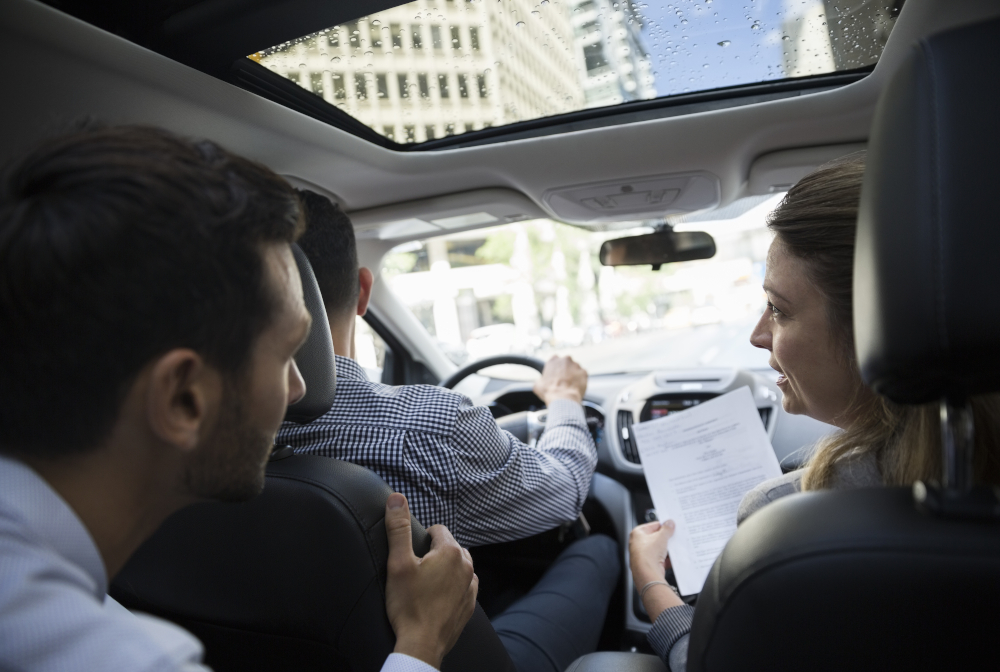 Business People Carpooling And Discussing Paperwork In Car