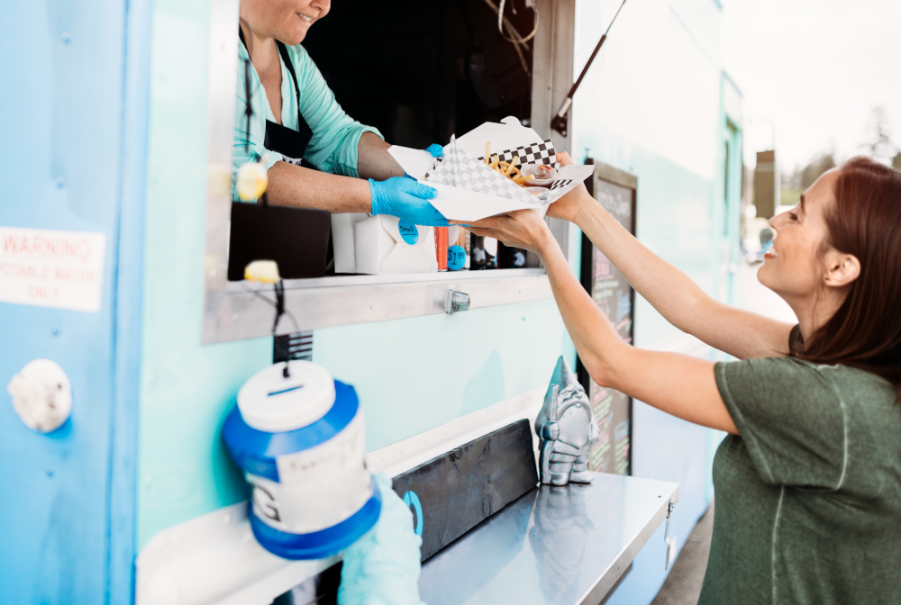 Woman Receiving Order At Food Truck