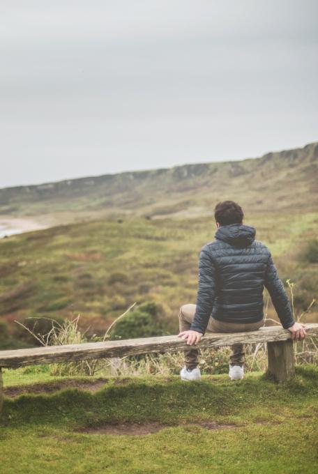 Man Sitting On Bench , Rear View ,enjoying Oceanic Coast View