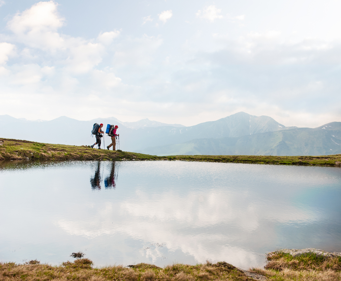 http://Trekkers%20Passing%20By%20A%20Calm%20Lake%20In%20The%20Mountains