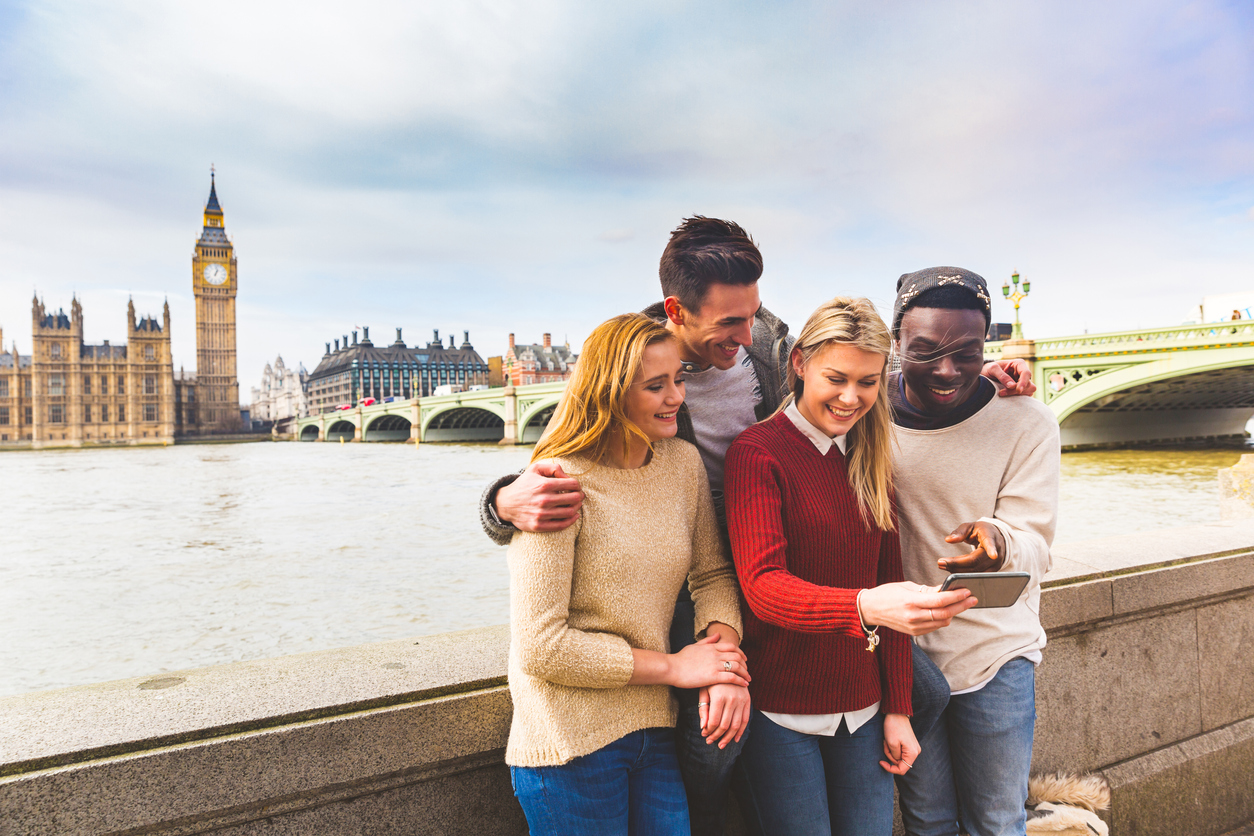 Friends Having Fun With Smartphone At Big Ben In London
