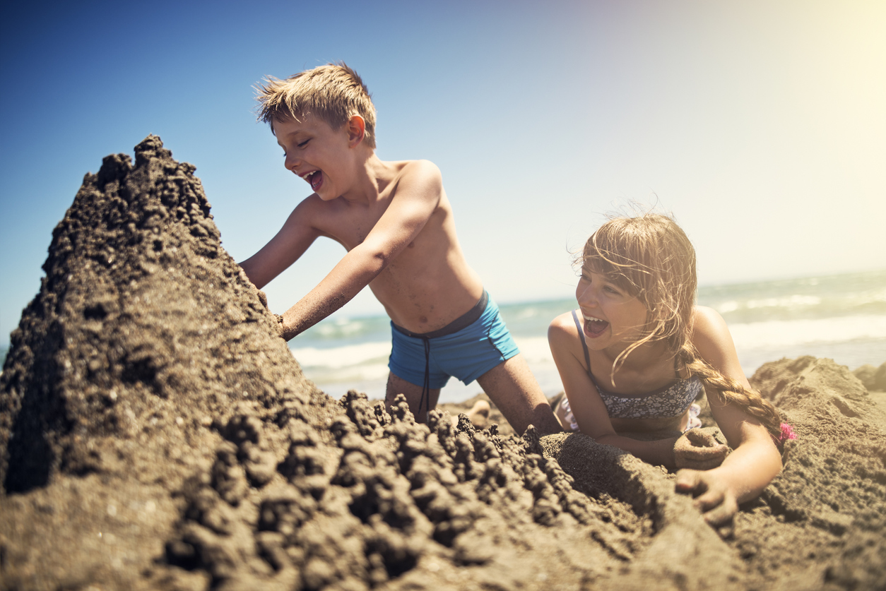 http://Brother%20And%20Sister%20Building%20A%20Sandcastle%20On%20Beach